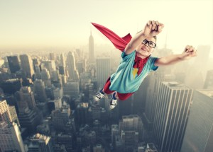Little superhero boy flying in the air