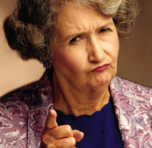 elderly female woman with shorter graying hair wearing a purple jacket and blue shirt frowns and gives the camera or imaginary person a disapproving look while she shakes her finger and appears to be scolding someone
