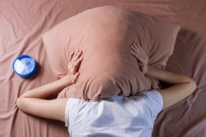 woman cover her head with pillow