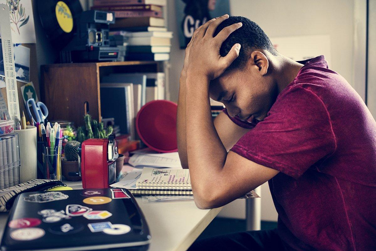 Frustrated teenage boy working too hard