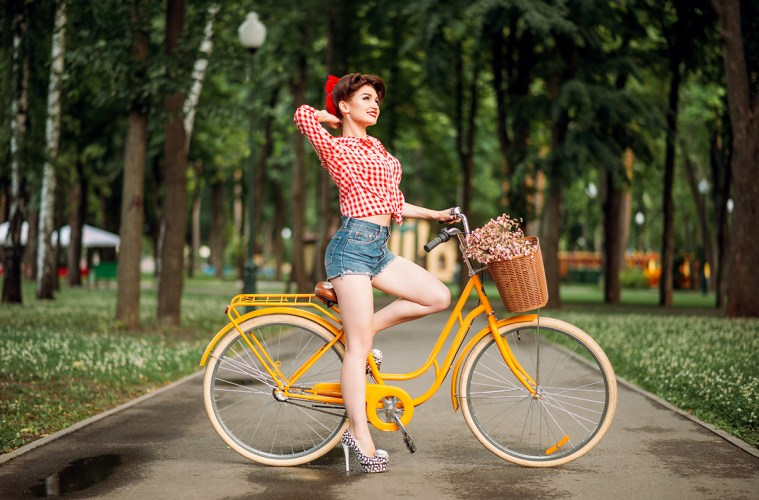 Pin-up girl on bicycle, vintage american fashion