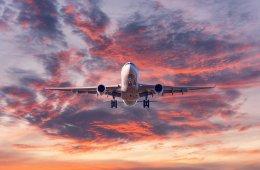 Landing passenger airplane at colorful sunset