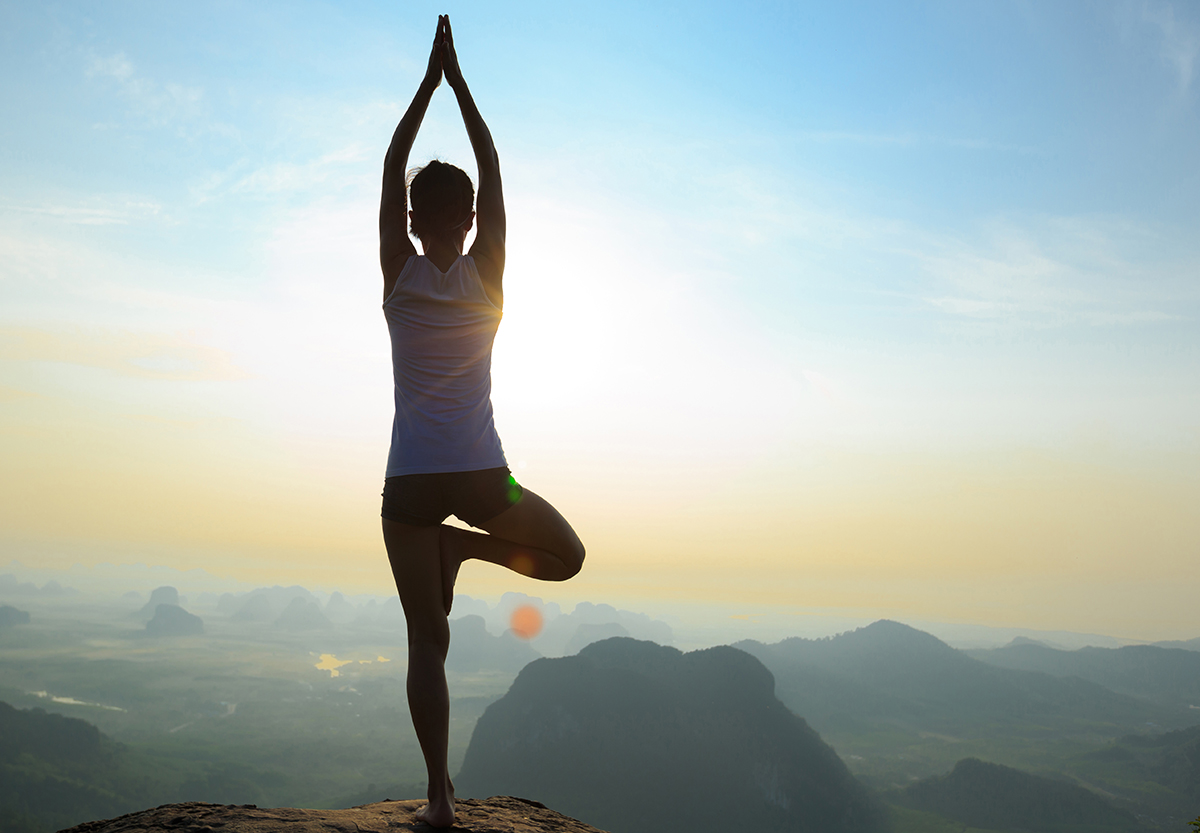 Woman doing yoga on a mountain