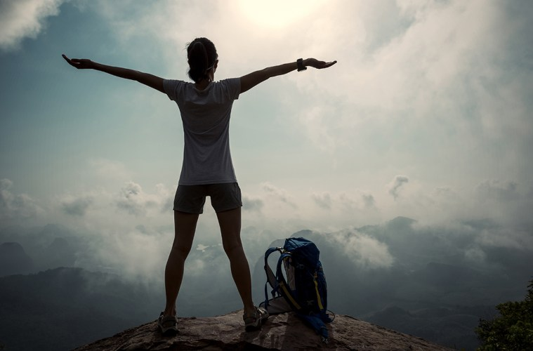 cheering successful woman hiker open arms on sunrise mountain top