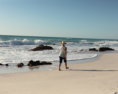 Rear view of a senior Caucasian woman at the beach in the sun, wearing a sun hat and walking barefoot in the sand and smiling, with sea and blue sky in the background