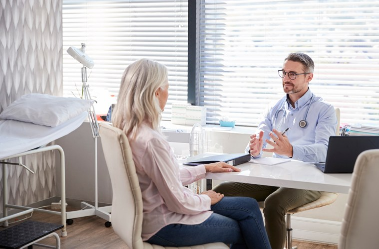 Mature Female Patient In Consultation With Doctor Sitting At Desk In Office