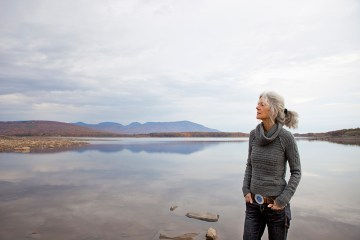 A woman looking out over the water on the shores of a calm lake.