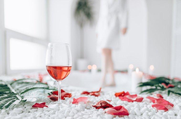 Woman dips legs into the bath, rose petal decor