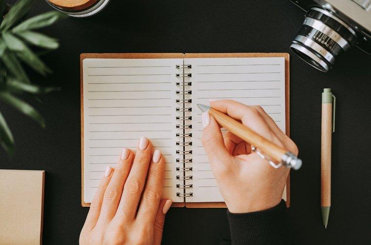 Flat lay woman's hand writes down addresses