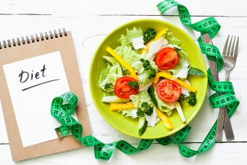 Healthy eating and Diet concept. Green Plate with fresh vegetables salad and measurement on wooden table.