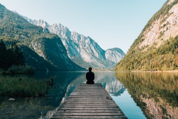 Woman meditating on dock