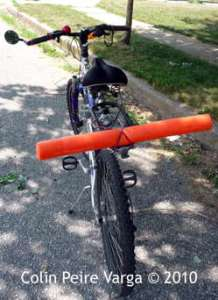 A bright orange noodle tied across the back of a bicycle