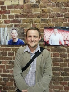 George in front of photos of Chris and Paul