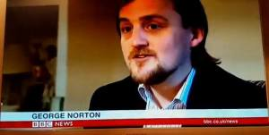 George on BBC News, with name captioned