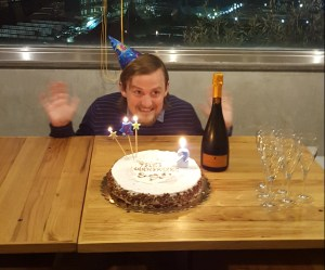 George peering over the edge of a table to see his second birthday cake and a bottle of Prosecco