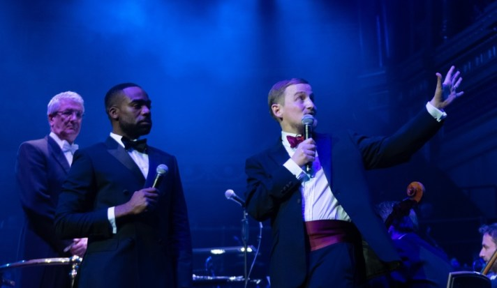 George and Ore Oduba onstage in black tie, with George waving his left arm up towards the choir and speaking into the microphone