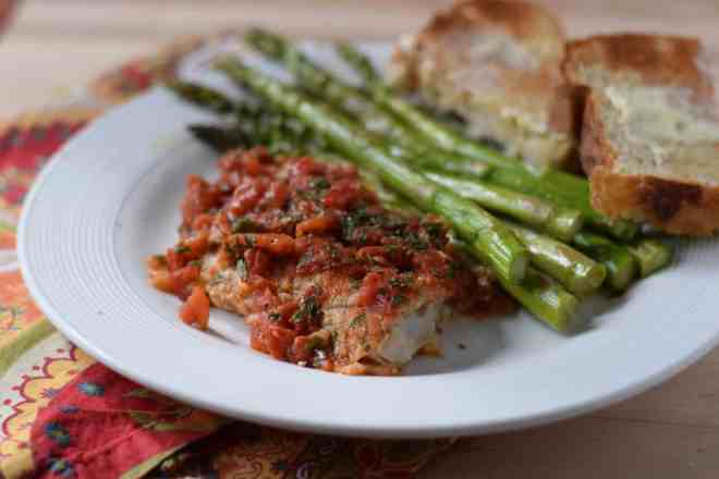 Baked fish topped with tomatoes next to roasted asparagus and two slices of whole wheat bread and butter.