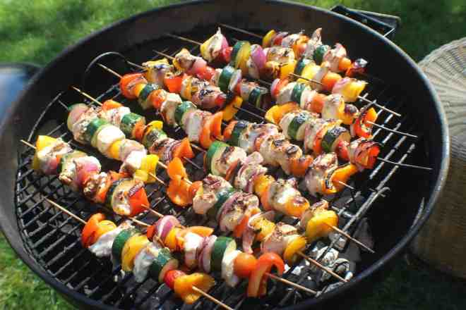 Meat and vegetables on skewers on a charcoal grill.