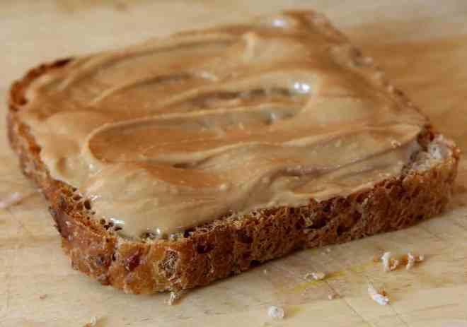 Piece of whole grain bread spread with peanut butter.