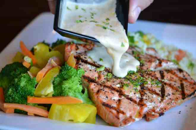 Grilled salmon with sauce and steamed vegetables.