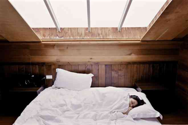 Woman sleeping under white comforter.