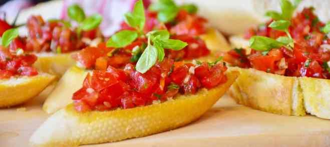 Chopped tomatoes, basils and herbs on top of sliced baguette.