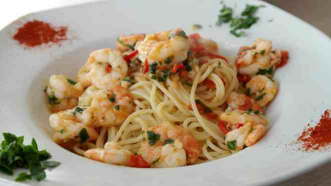 Bowl of white pasta topped with shrimp and chopped parsley.