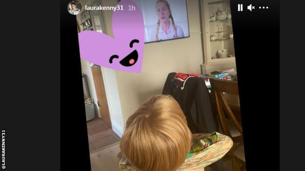 The back of a child's head, with the child watching Laura Kenny on television