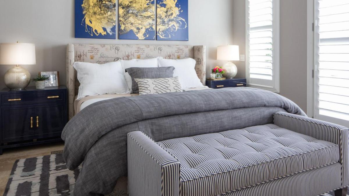 Luxury bedding, grey spread and grey fabric bench at the end of the bed