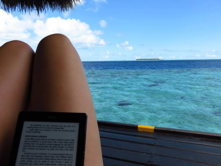 Maldives Overwater Villa deck reading an e-reader