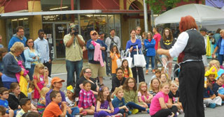 Can you find Robert Dokes taping the street magician doing her thing for the kids?