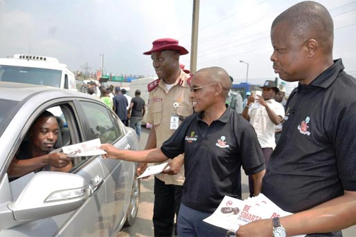 L-R FRSC Sector Commander, Lagos state, Hyginus Omeje; Managing Director, Guinness Nigeria Plc, Mr. Peter Ndegwa handing out a Responsible Drinking flyer to a motorist and Corporate Relations Director, Guinness Nigeria Plc, Sesan Sobowale during the flag-off of the 2016 Guinness FRSC Ember months campaign at the Ketu Garage in Lagos