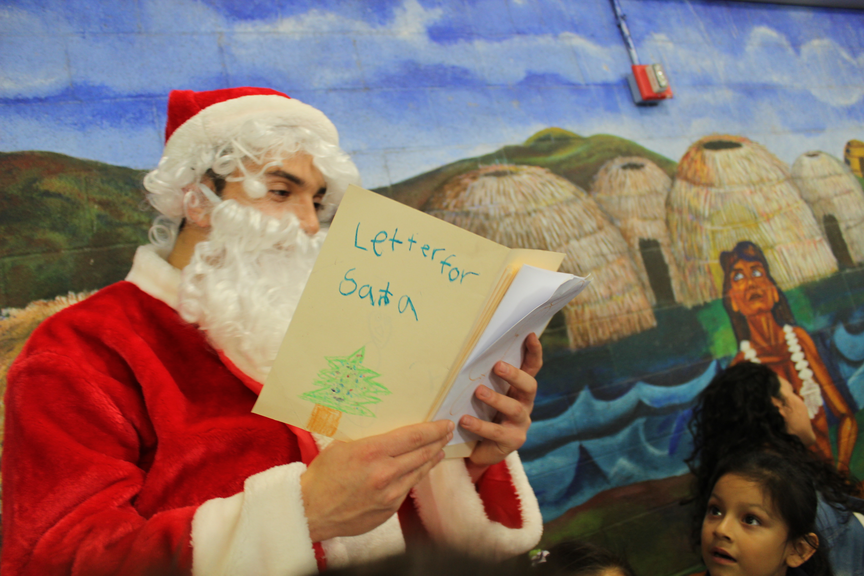 Hedvat reads aloud letters to Santa, written by Albion students, during lunc.