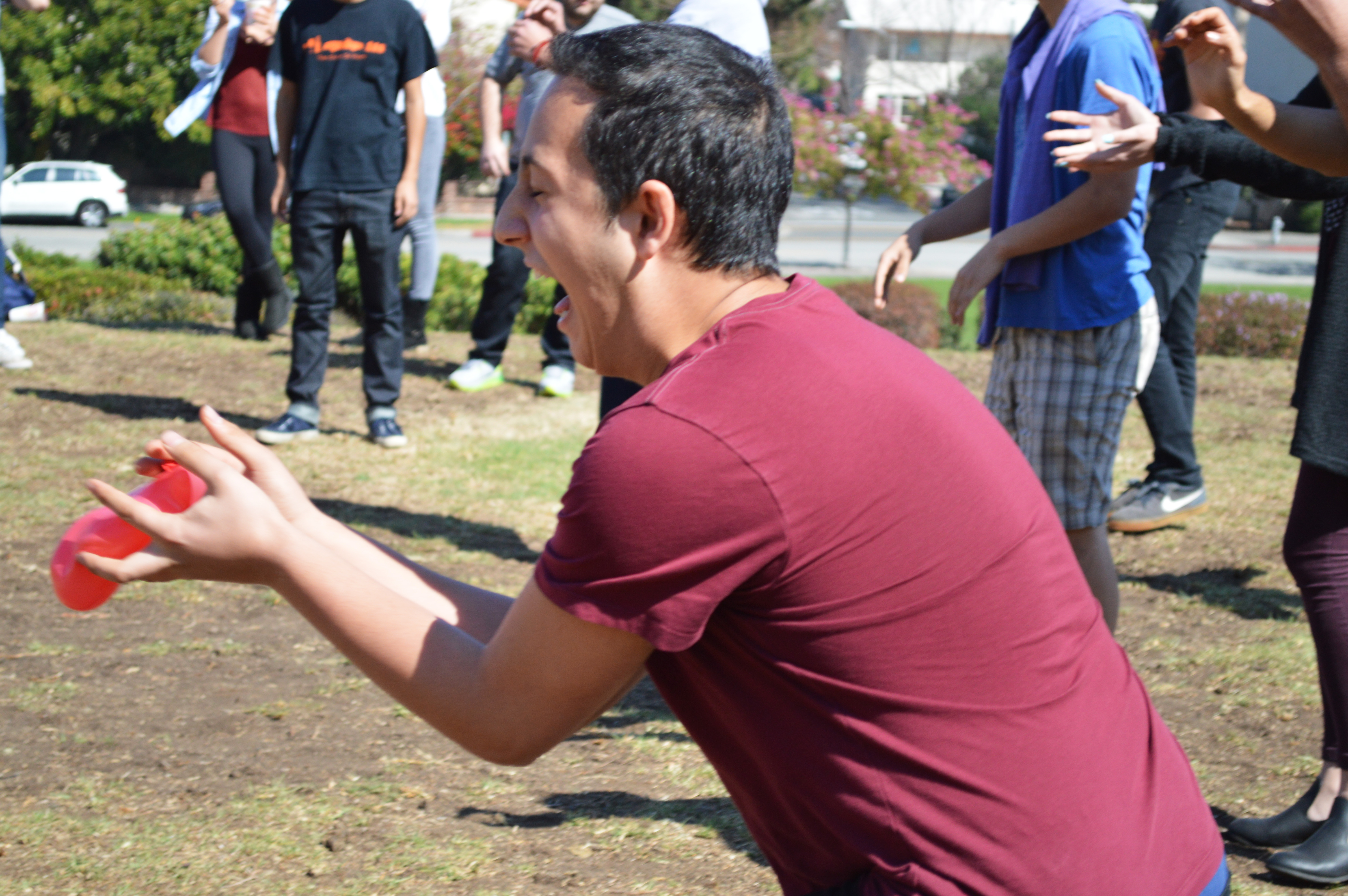 A junior reacts as he successfully catches his partner's water balloon toss, advancing with his partner to the next level.