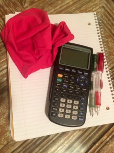 A lonely textbook cover, surrounded by other school supplies, shrivels in the absence of an AP Statistics book.