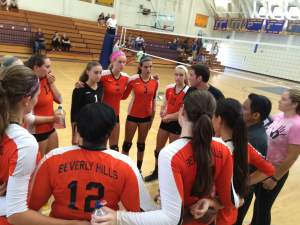 The girls varsity volleyball team reevaluates their strategy in between their games.