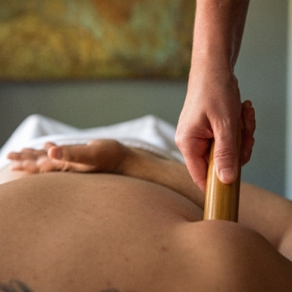 bamboo stick being used on a client during bamboo massage