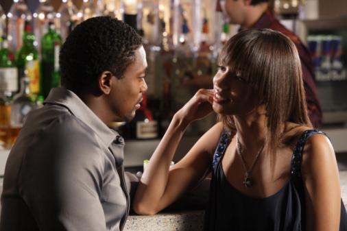African couple talking at bar