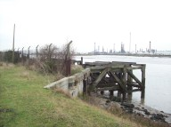 What is believed to be a jetty for shipping imports (probably for construction of the refinery) which is mostly burnt and decayed into the water. it appears to be all-wood