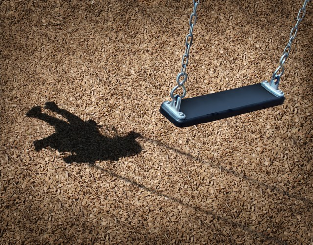 Missing child concept with an empty playground swing and the shadow of a little girl on the park floor as a symbol of children losing their childhood and being lost as in a failed adoption or youth despair caused by family violence.