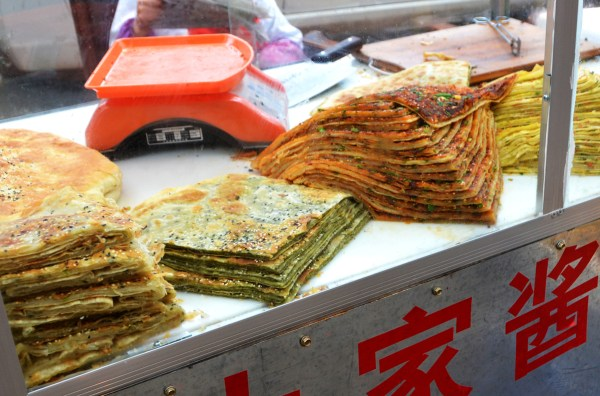 A very popular local dish, this savory pancake is called Gou Jiao Niao or Gou Jiao Niao Bing. It's often multilayered with powdered fenugreek leaves and turmeric but also seasoned with sesame seeds, scallions and chili powder.