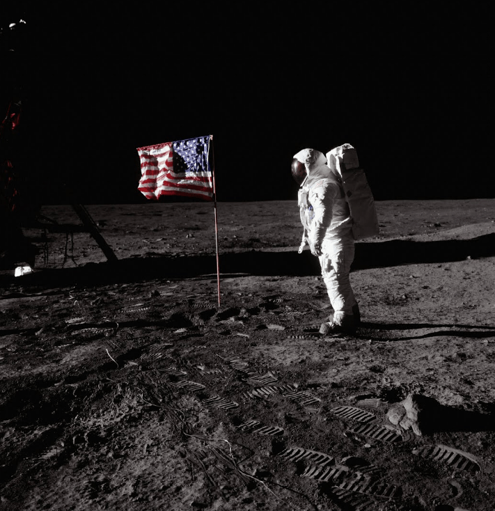 Buzz Aldrin standing on the moon after planting the American flag.