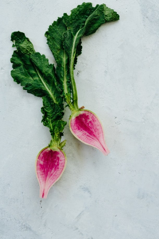 Two watermelon radish halves on plaster surface