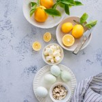 ingredient with lemons in bowl, bowl of butter, four eggs on plate, almond bowl, and striped kitchen towel