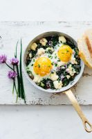 frying pan with ramp ricotta baked eggs two slices of sourdough chives and chive blossoms