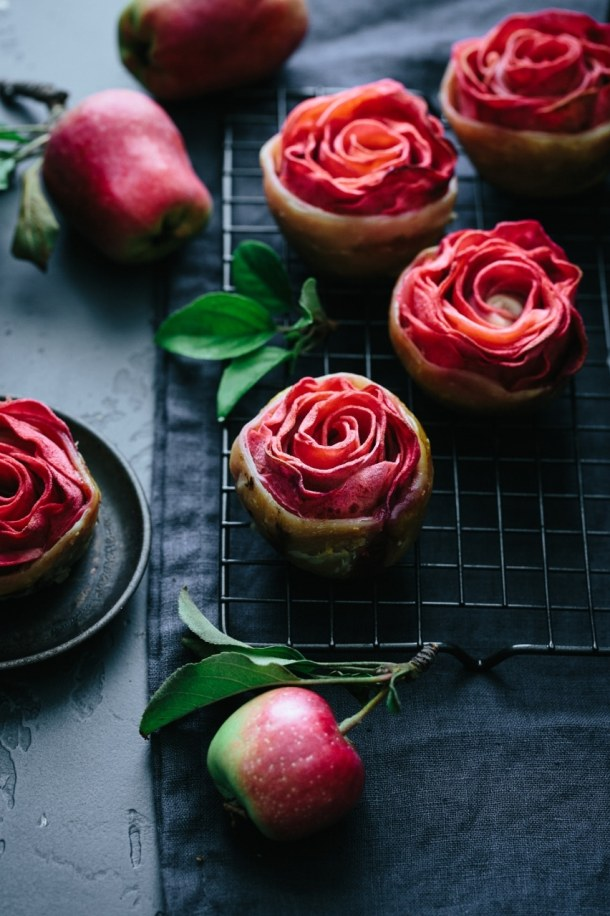 four hidden rose apple tarts on cooling rack and one on a plate
