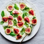 a plate of fig caprese salad with fresh figs, mozzarella, and basil