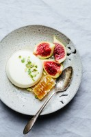 a plate of orange blossom panna cotta with figs, honeycomb, and pistachios