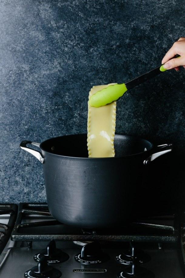 large pot with tongs holding lasagna sheet