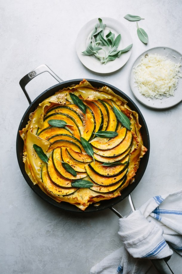 skillet pumpkin ricotta lasagna with a plate of cheese and a plate of fresh Parmesan cheese
